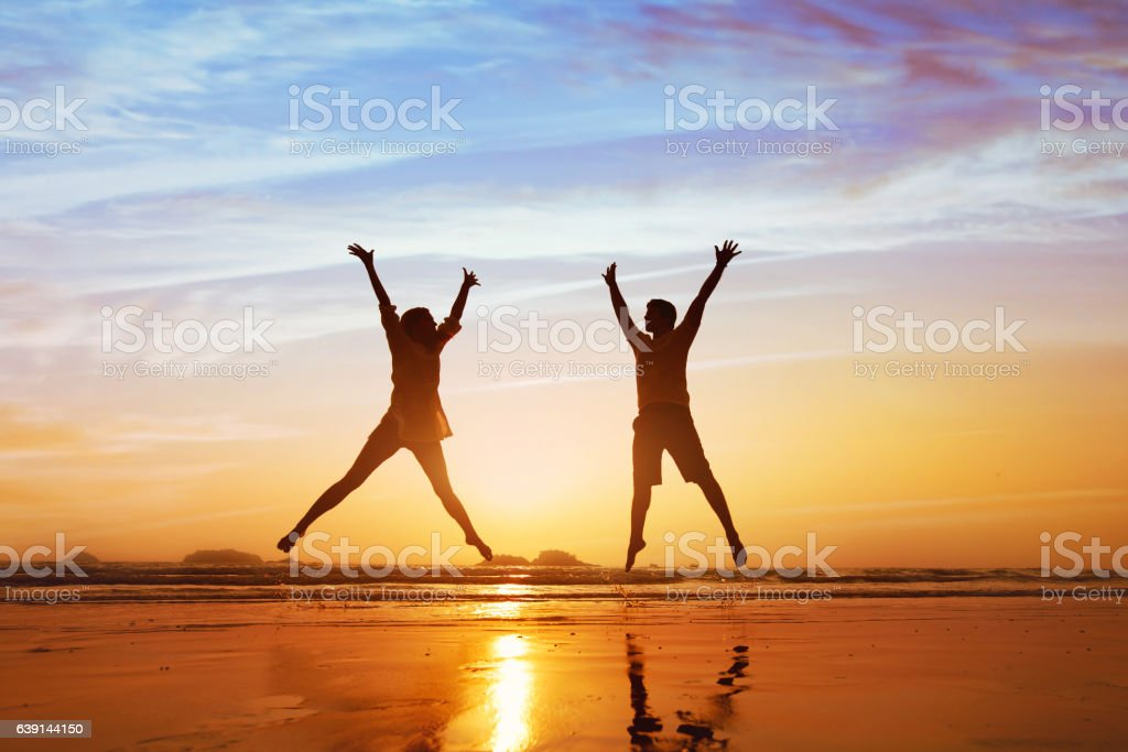 happy couple jumping on the beach at sunset stock photo