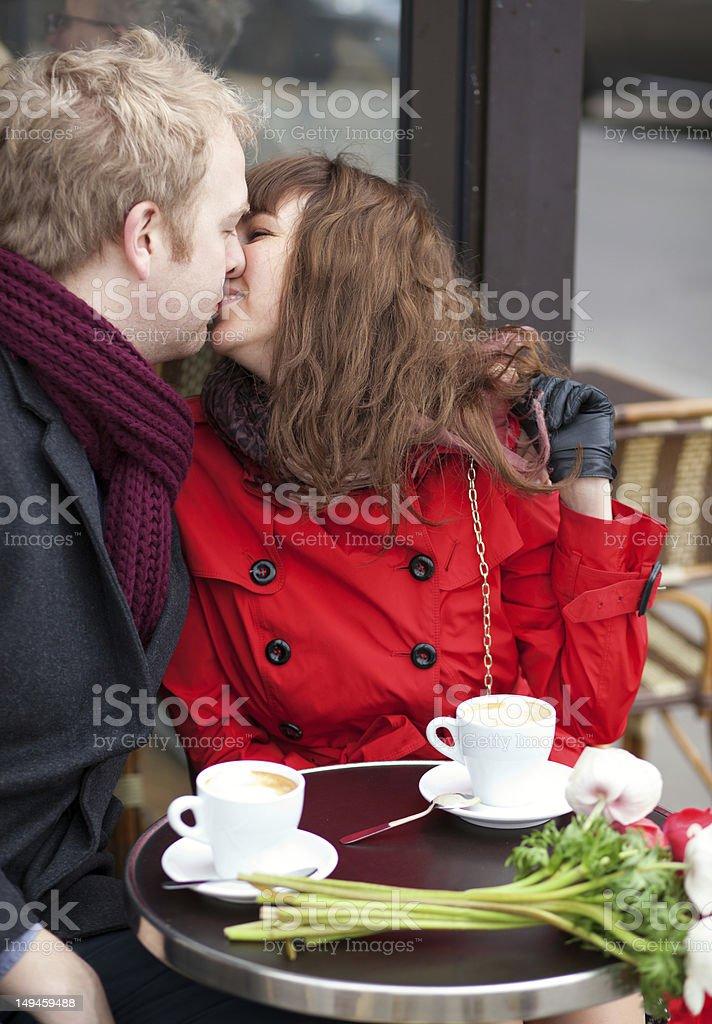 Happy couple kissing in Parisian cafe royalty-free stock photo