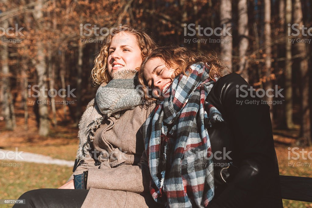 Happy couple laughing on the bench by the forest stock photo