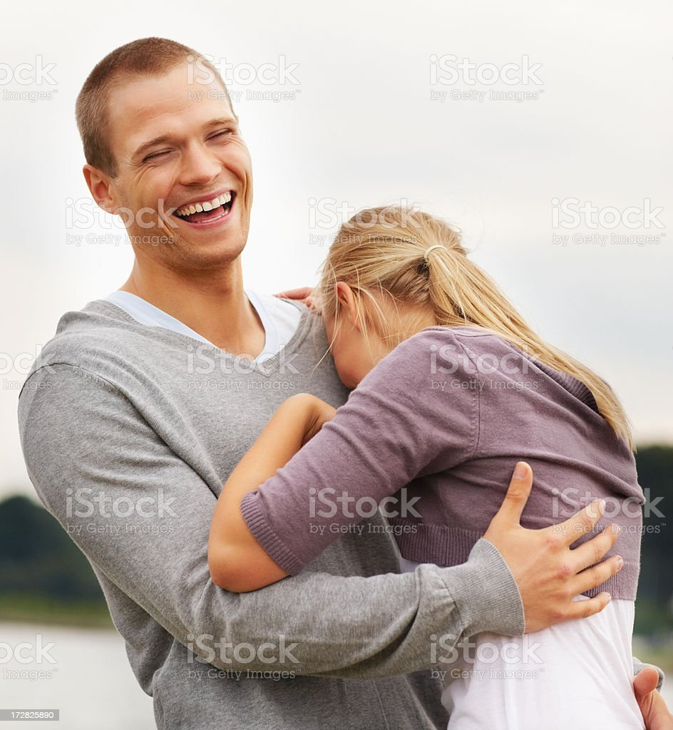Happy couple laughing outdoors, embracing eachother stock photo