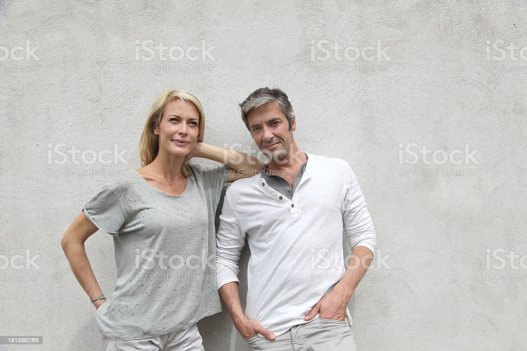 Happy couple leaning on white wall royalty-free stock photo