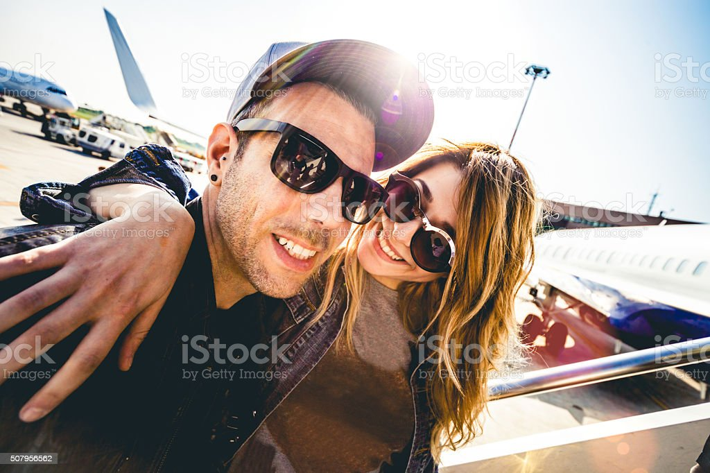 Happy Couple leaving for vacations boarding on a plane stock photo