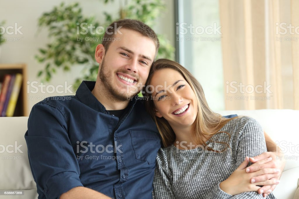 Happy couple looking at camera at home stock photo