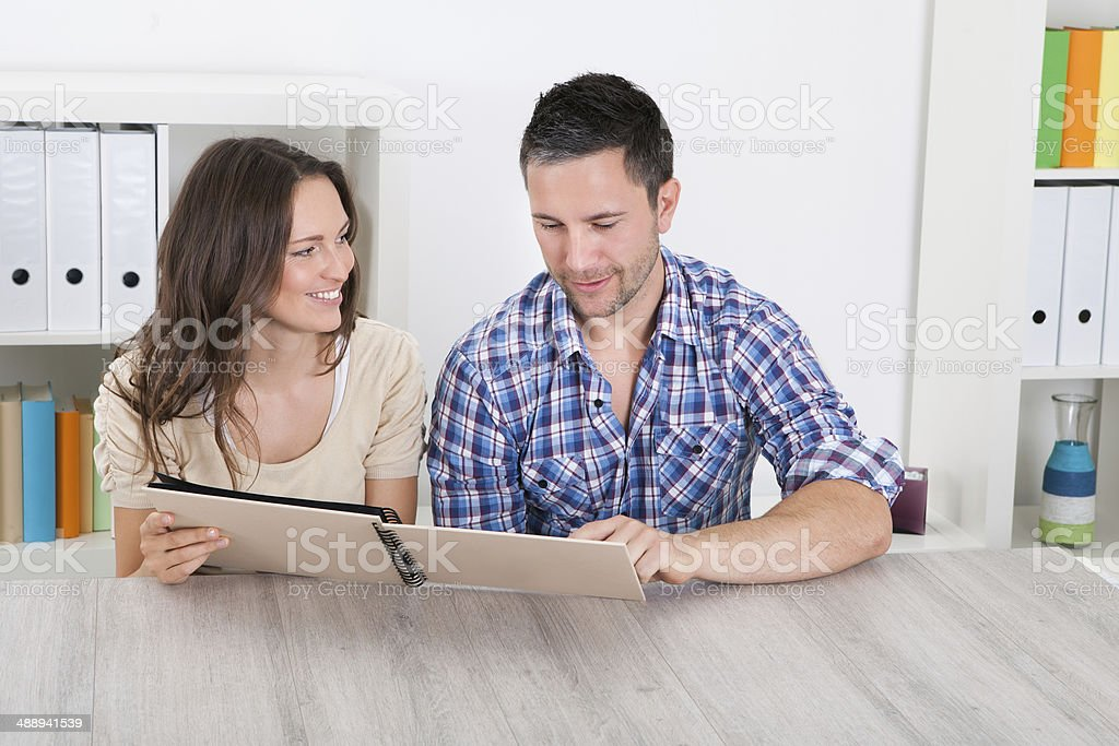 Happy Couple Looking At Photo Album royalty-free stock photo