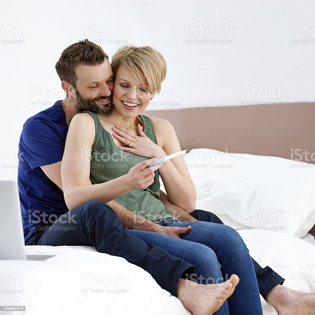 Happy couple looking at pregnancy test result stock photo