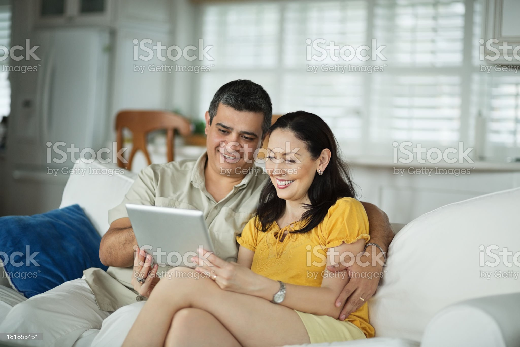Happy couple looking at smart tablet on a sofa royalty-free stock photo