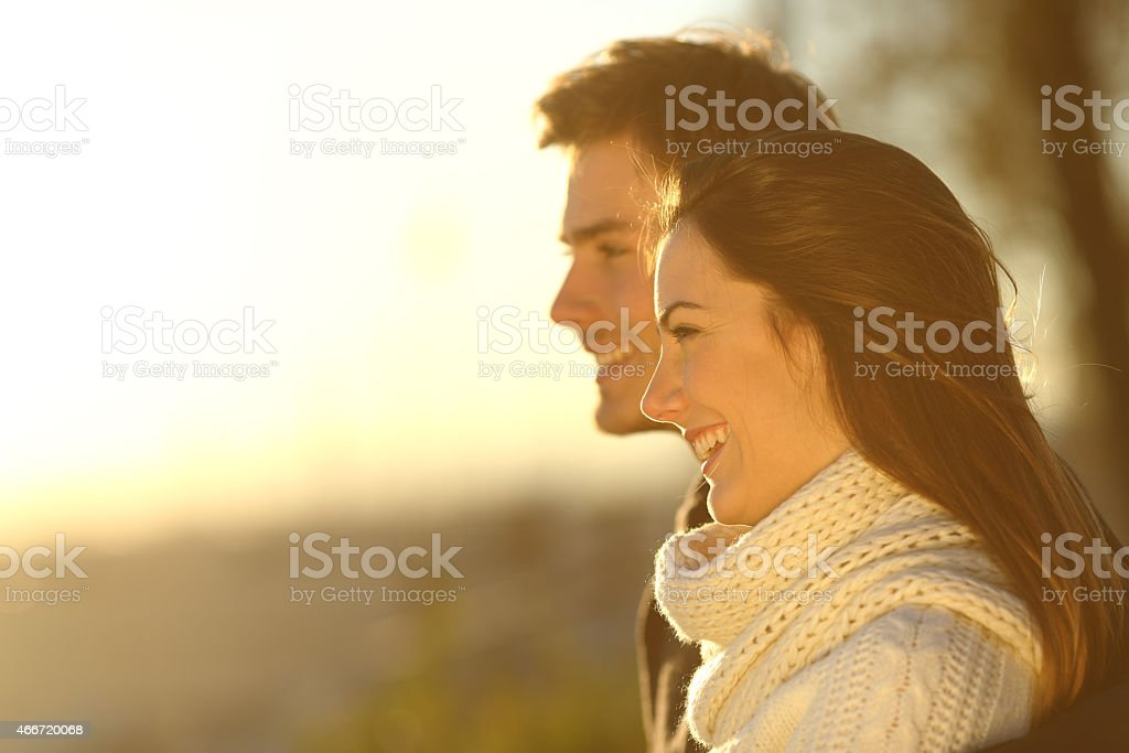 Happy couple looking at sunset in winter stock photo
