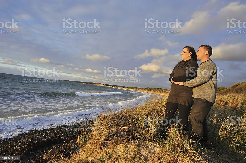 Happy couple looking at the sunset royalty-free stock photo