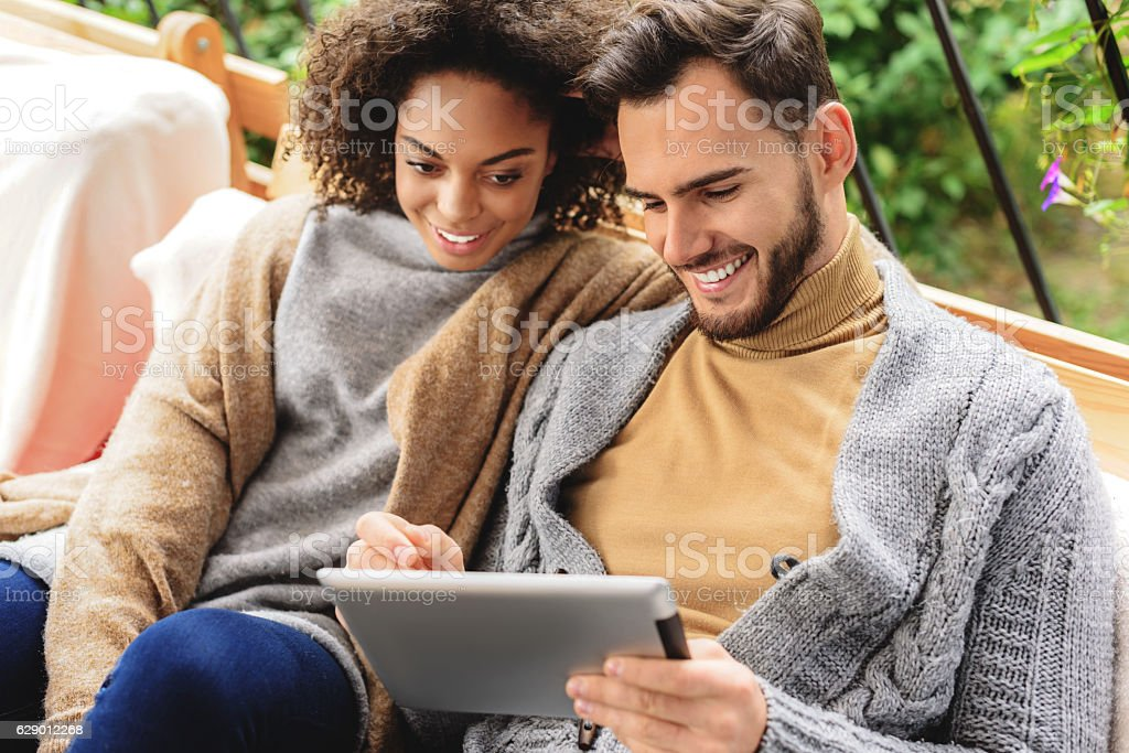 happy couple looking into a tablet stock photo