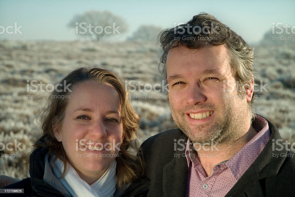 Happy couple looking into the winter sun stock photo