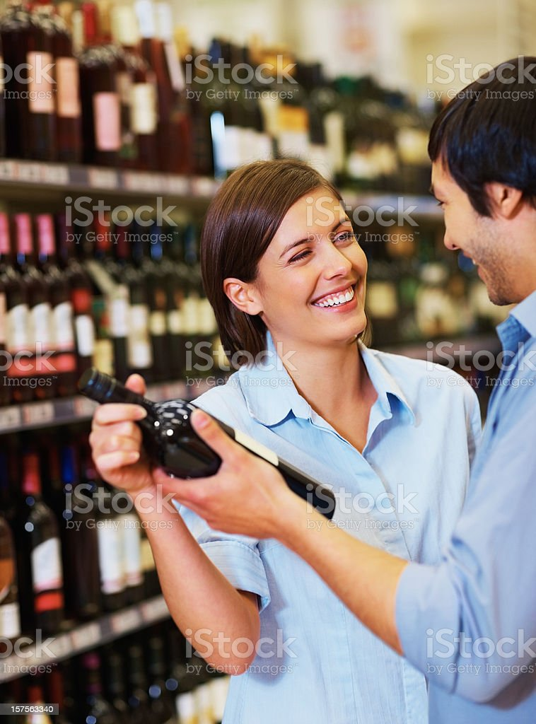 Happy couple looking out for a wine bottle royalty-free stock photo