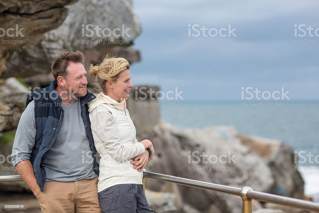 Happy couple looking out to sea stock photo