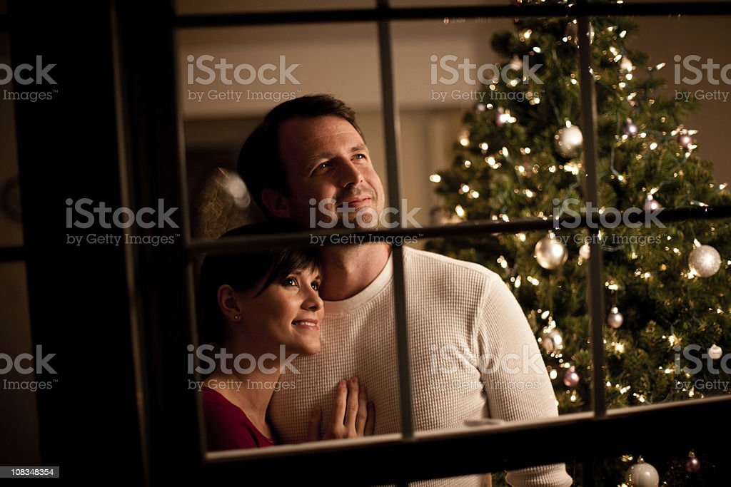Happy Couple Looking Out Window with Christmas Tree Behind royalty-free stock photo