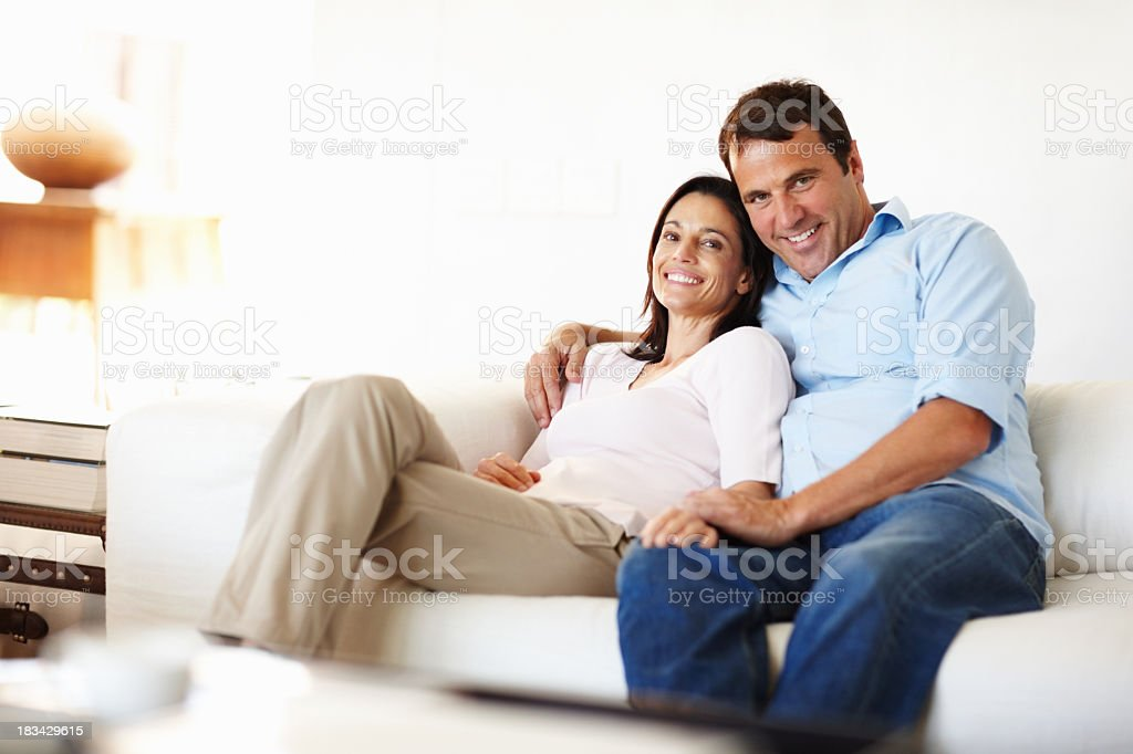 A happy couple lounging on the couch looking at the camera stock photo