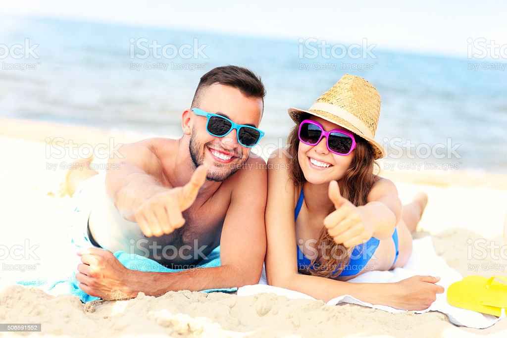 Happy couple lying on the beach stock photo