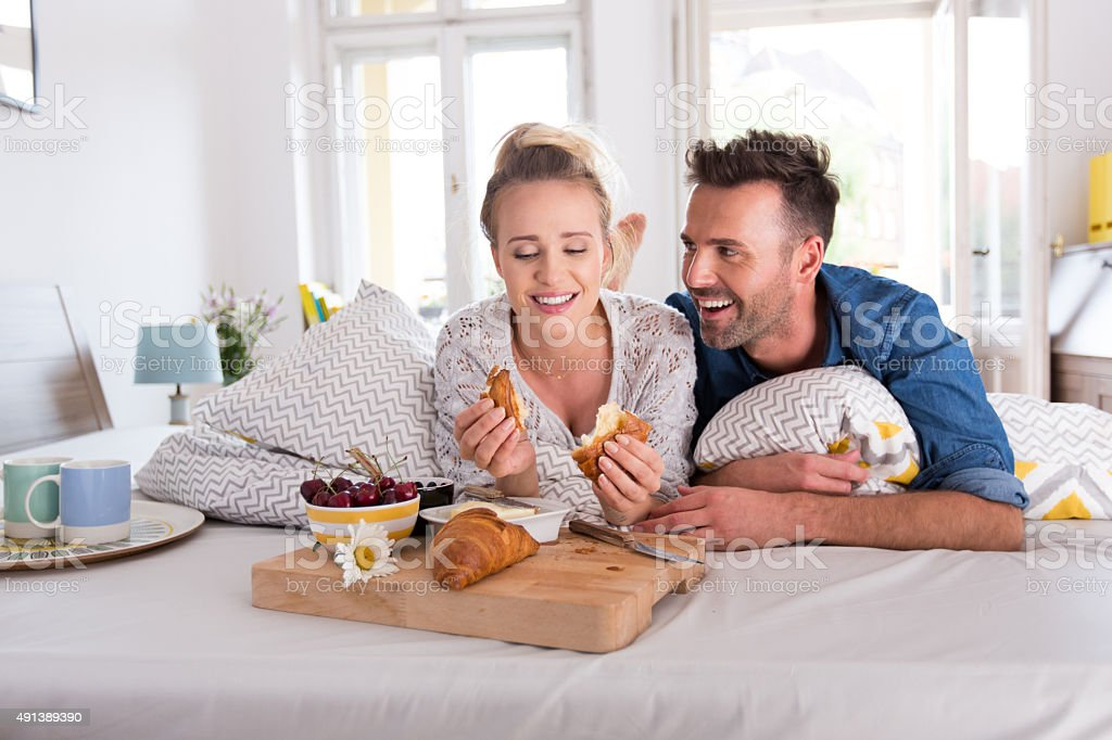 Happy couple lying on the bed, eating breakfast stock photo
