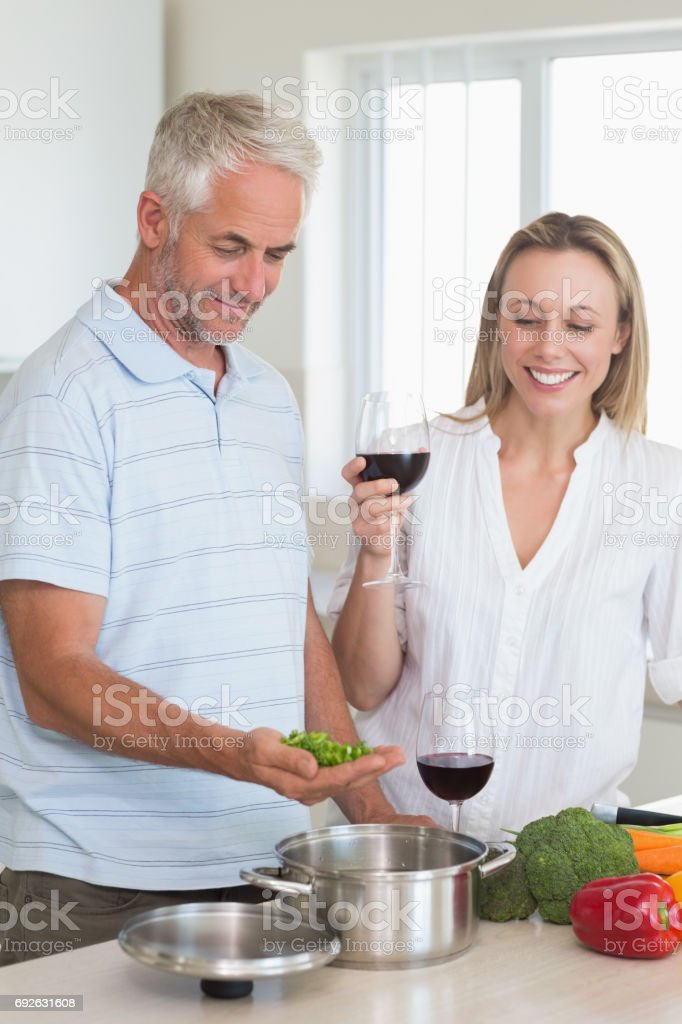 Happy couple making dinner together stock photo