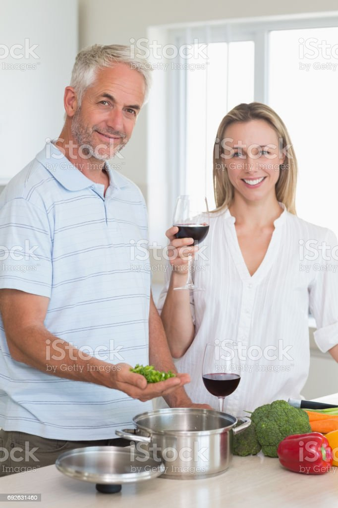 Happy couple making dinner together smiling at camera stock photo