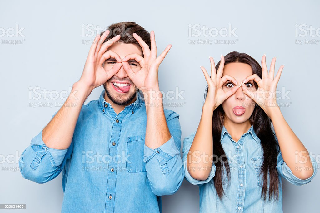 happy couple making glasses with fingers and showing tongue stock photo