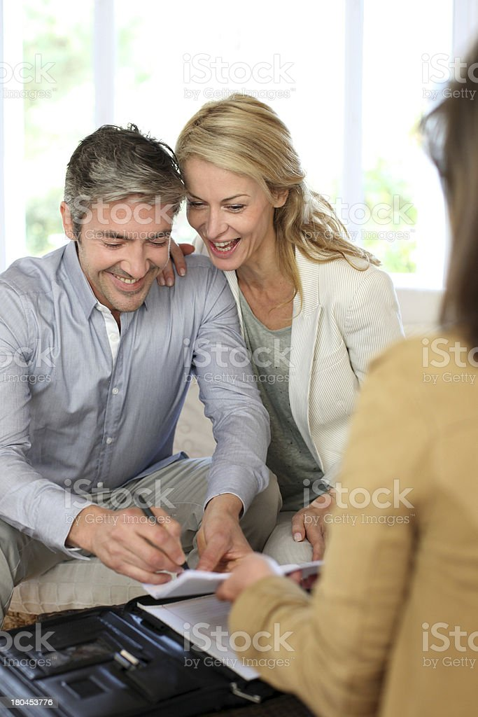 Happy couple meeting real estate agent to buy house royalty-free stock photo