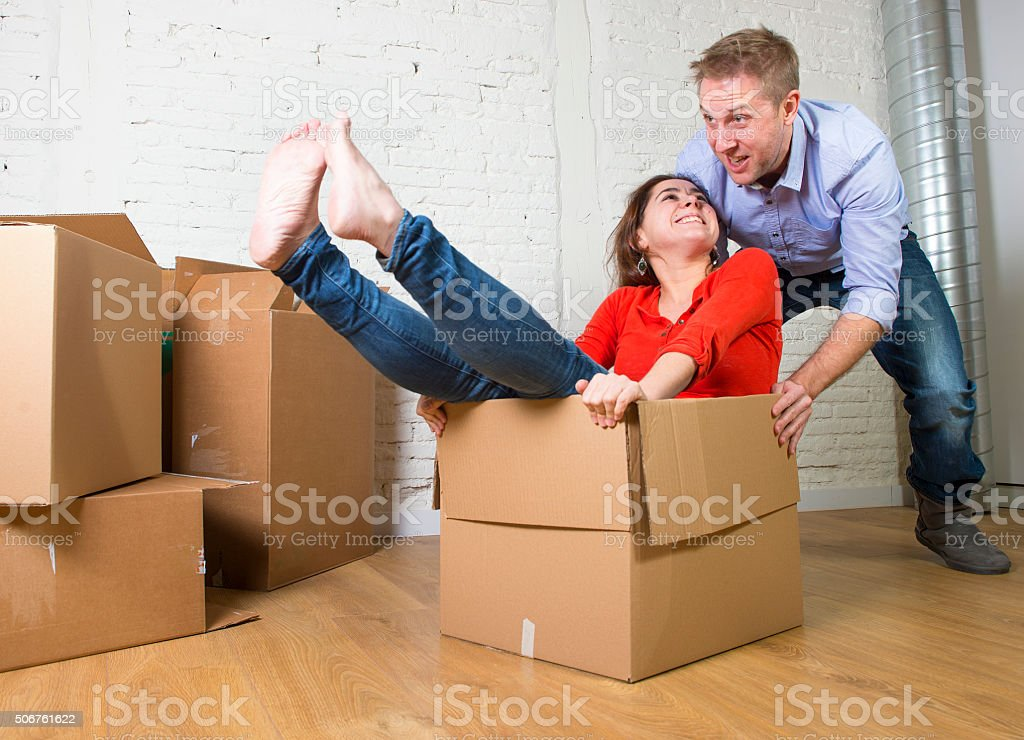young happy American couple unpacking having fun enjoying together...