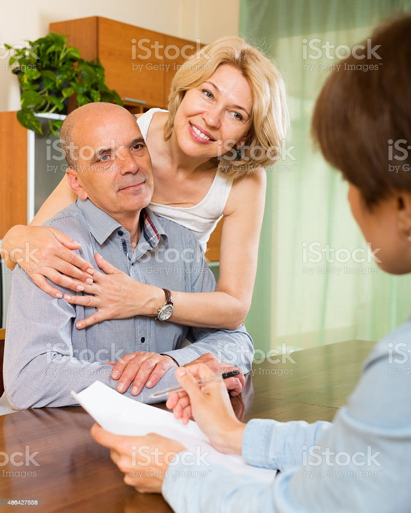 Happy couple of pensioners talking with manager stock photo