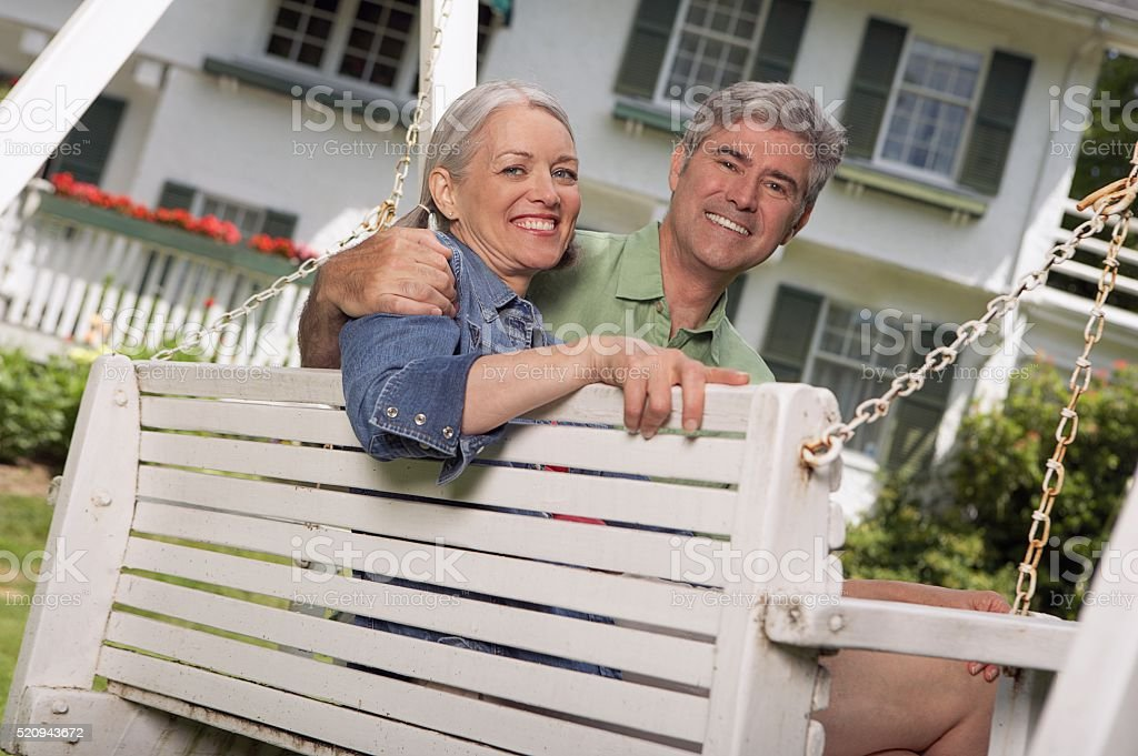 Happy couple on a bench stock photo