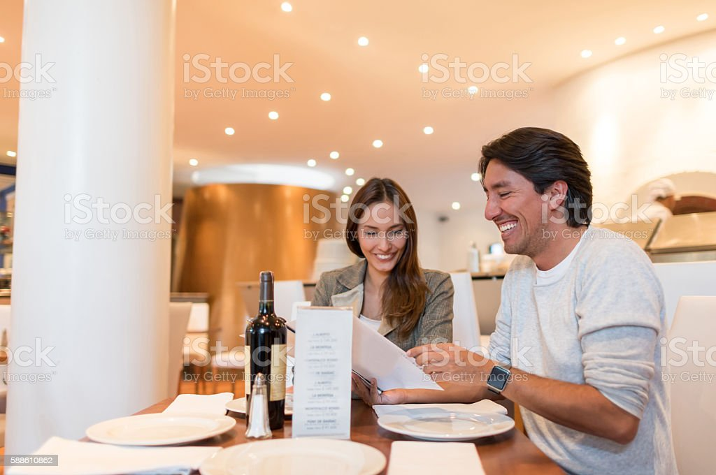 Happy couple on a date at a restaurant stock photo