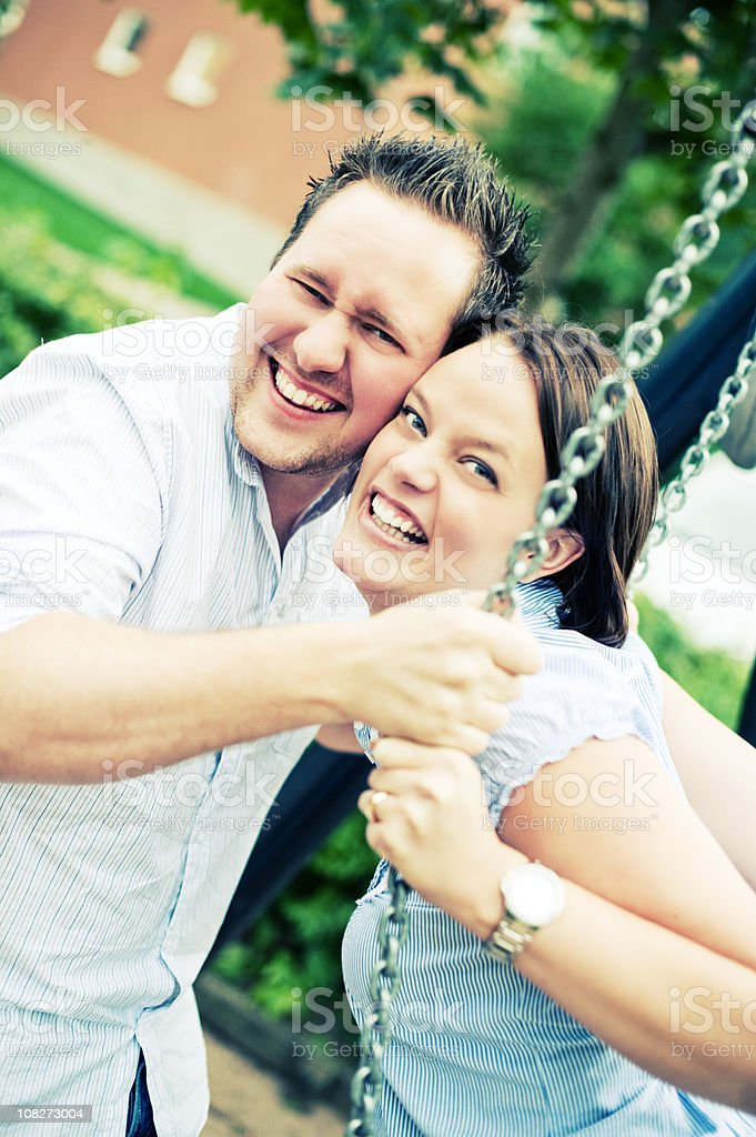 happy couple on a swing royalty-free stock photo