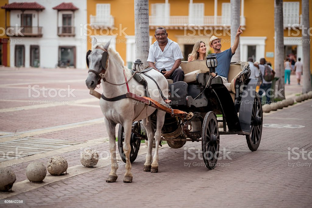 Happy couple on a tour riding on a carriage stock photo