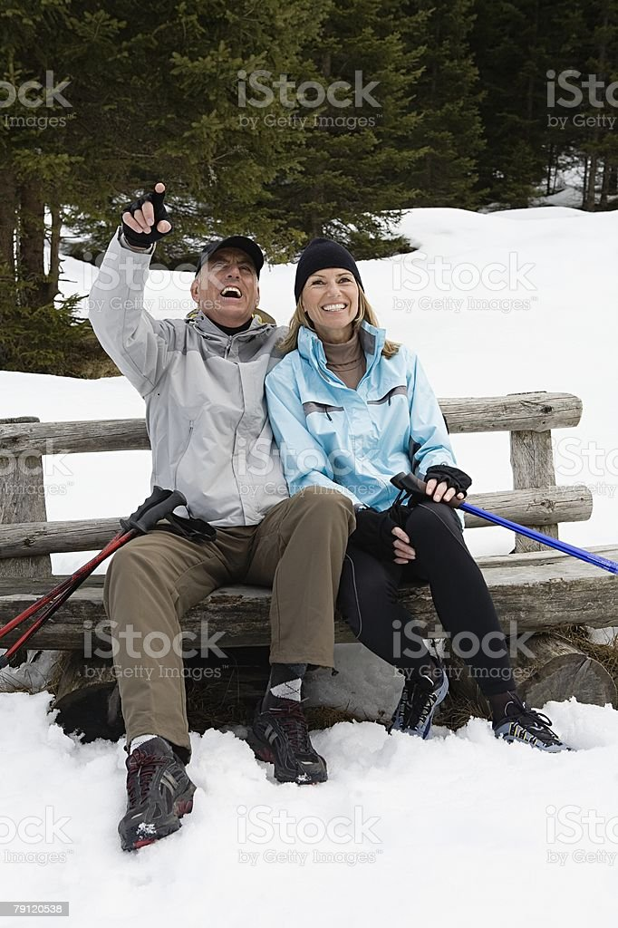Happy couple on bench in snow royalty-free stock photo