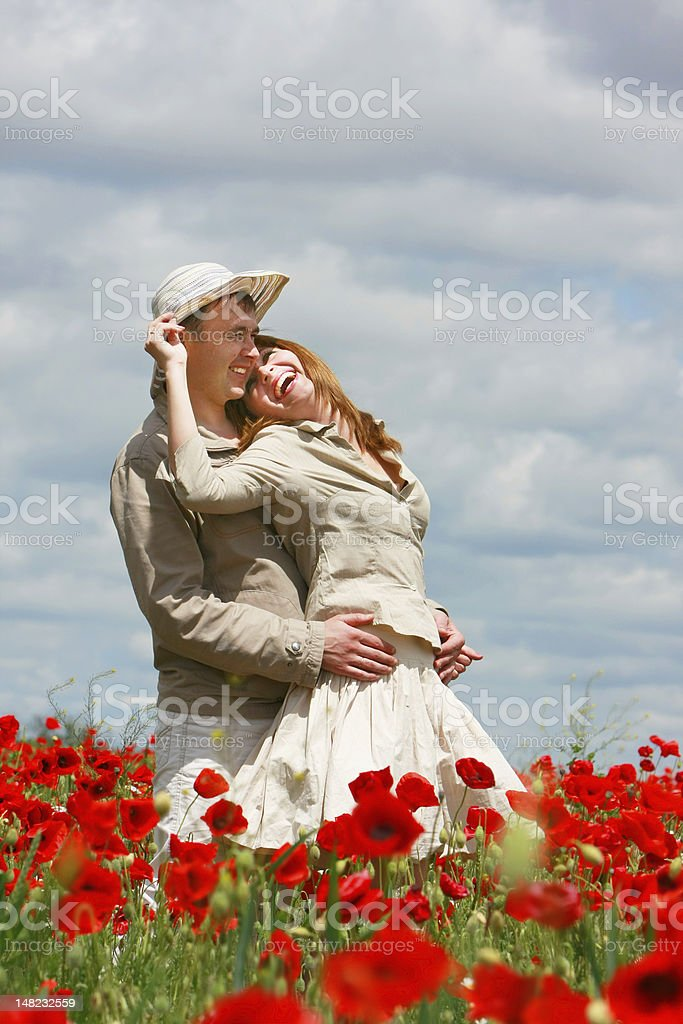 happy couple on red poppies field royalty-free stock photo