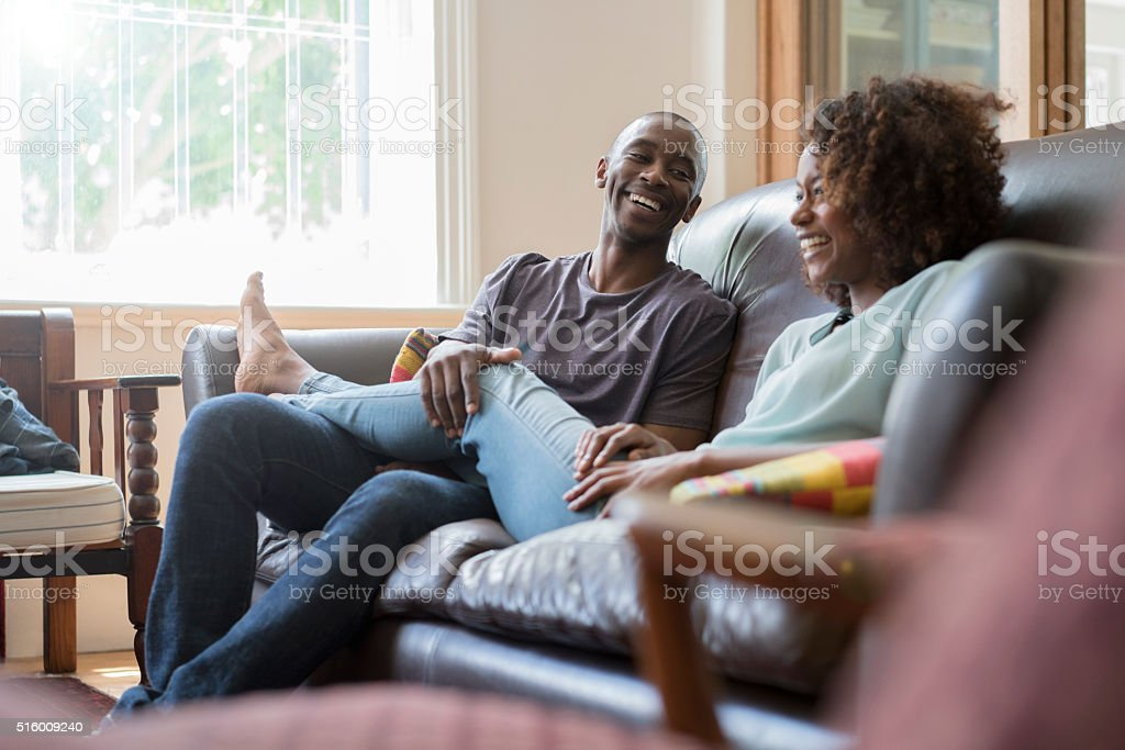 Happy couple on sofa at home stock photo