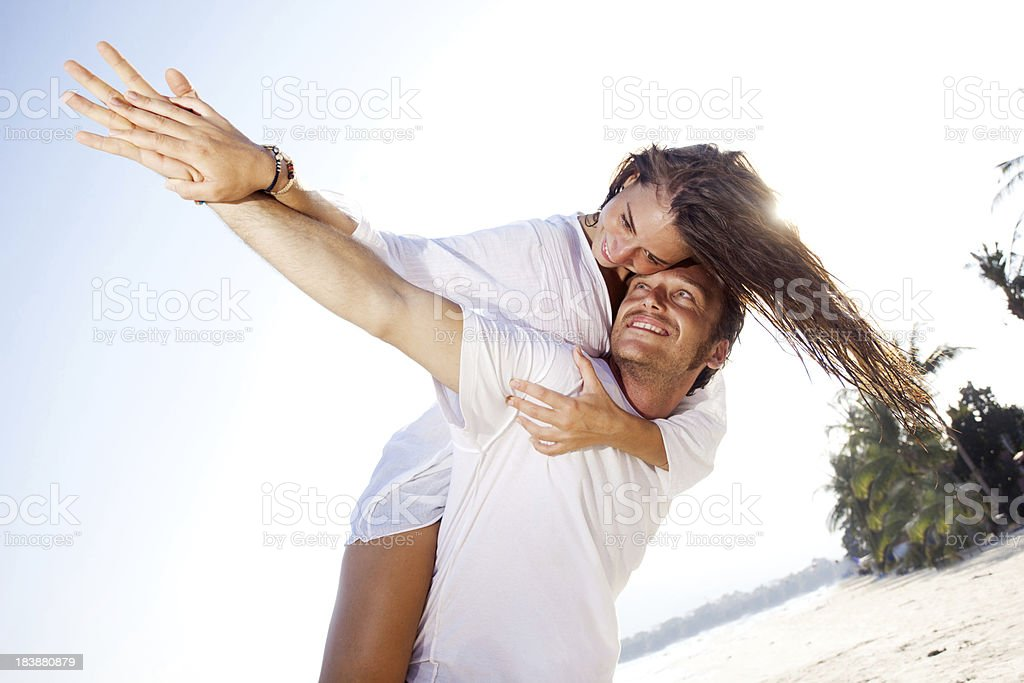 Happy couple on the beach doing piggy back ride. royalty-free stock photo