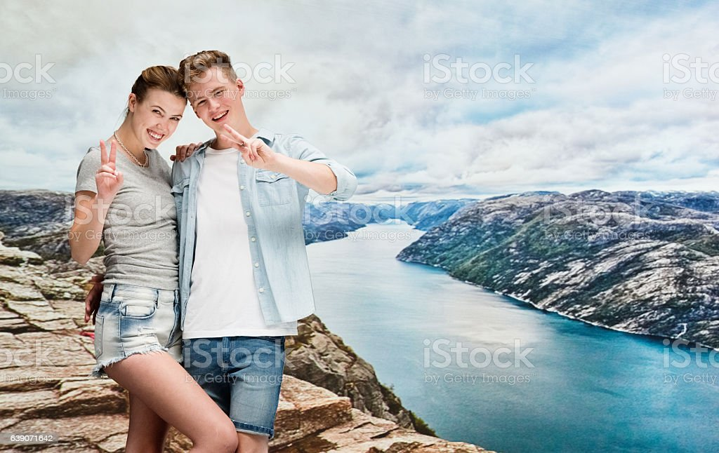 Happy couple on the cliff and giving victory sign stock photo