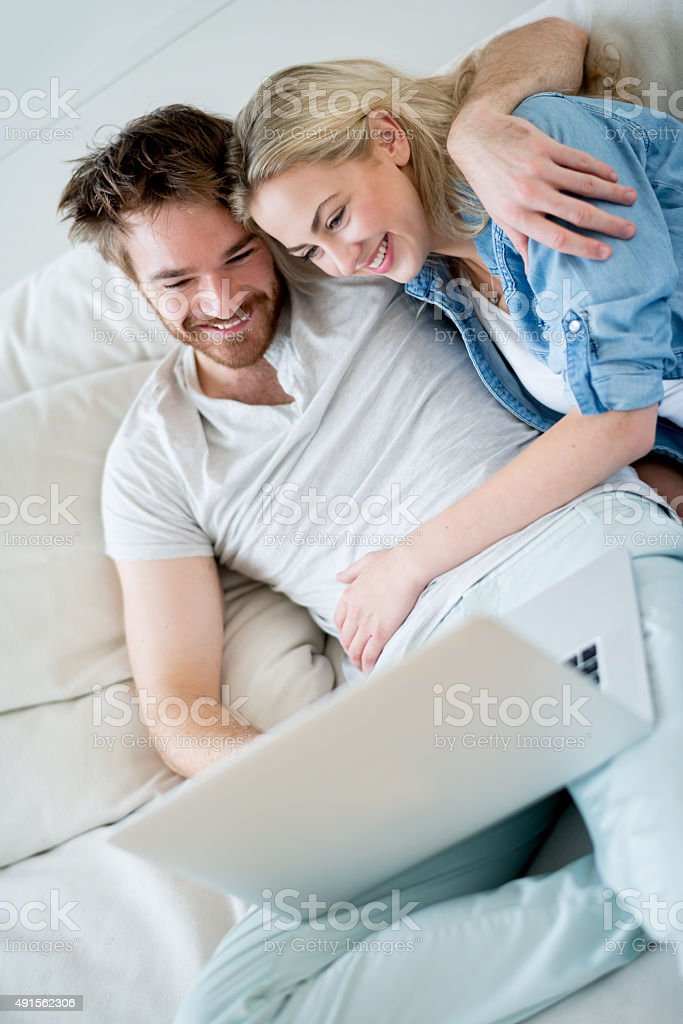 Happy couple online on a laptop computer stock photo