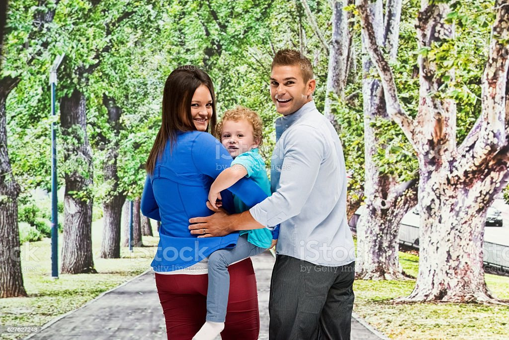 Happy couple outdoor with their baby stock photo