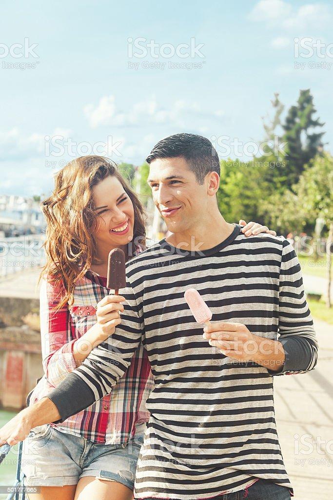 Happy couple outdoors eating ice cream stock photo