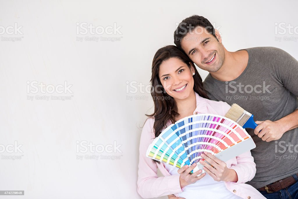 Happy couple painting a wall at home stock photo
