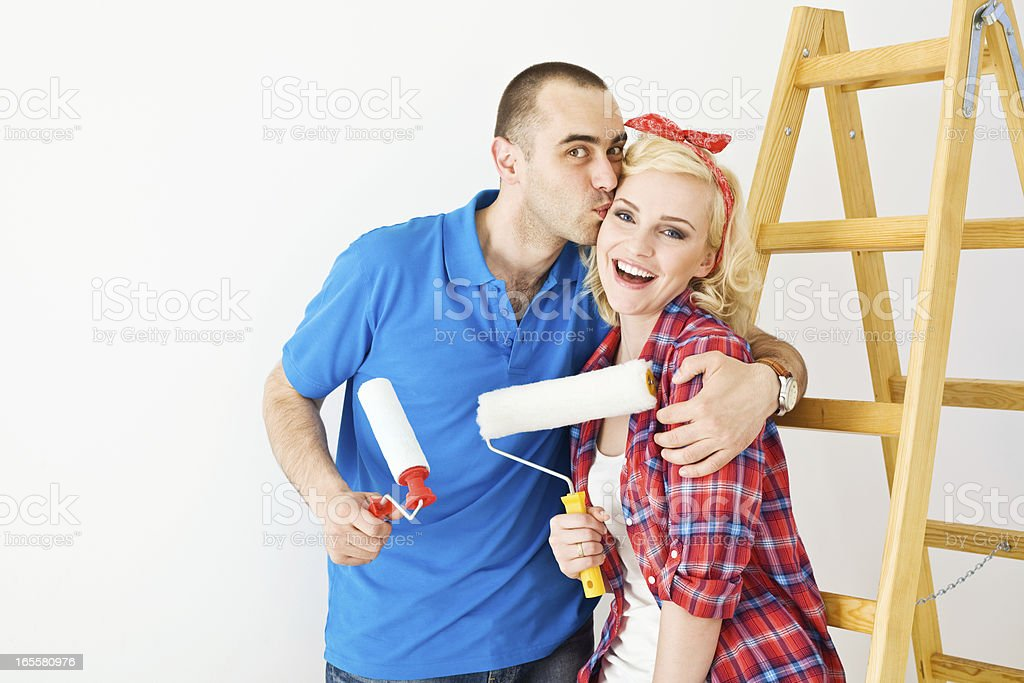 Happy couple painting a wall royalty-free stock photo