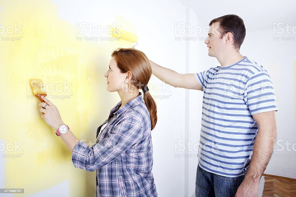 Happy couple painting a wall. royalty-free stock photo