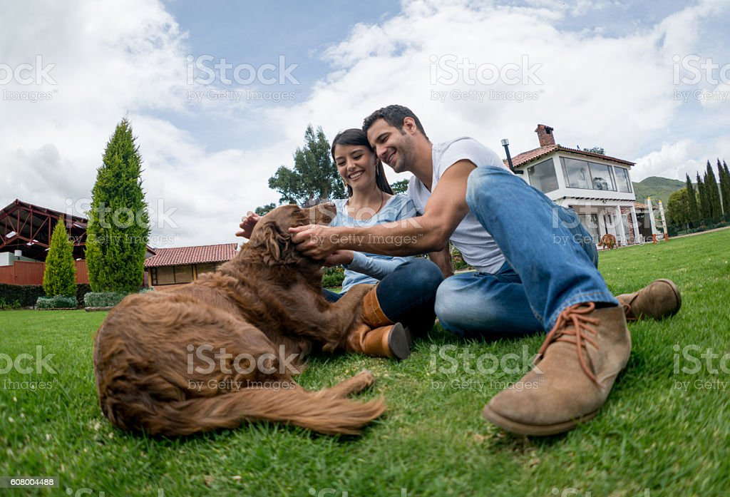 Happy couple pampering their dog stock photo