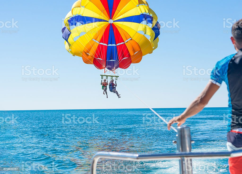 Happy couple Parasailing in Dominicana beach in summer stock photo