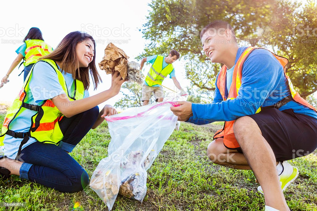 Happy couple participate in community cleanup day stock photo
