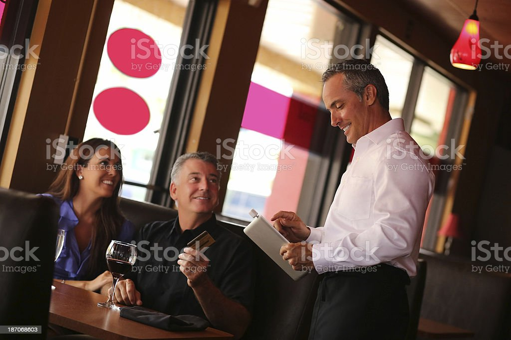 Happy Couple Paying By Credit Card In Restaurant stock photo