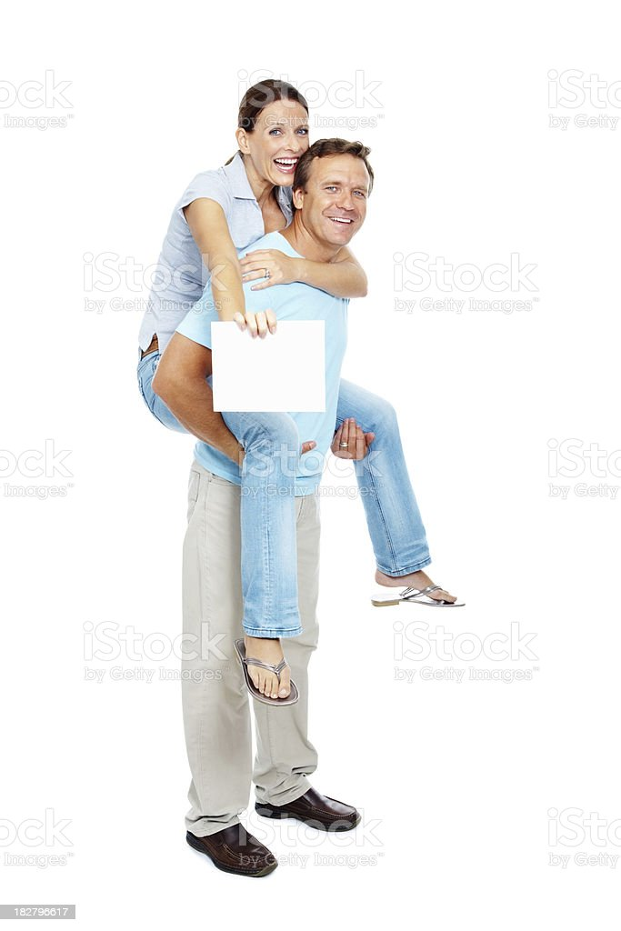 Happy couple piggybacking against and displaying placard royalty-free stock photo