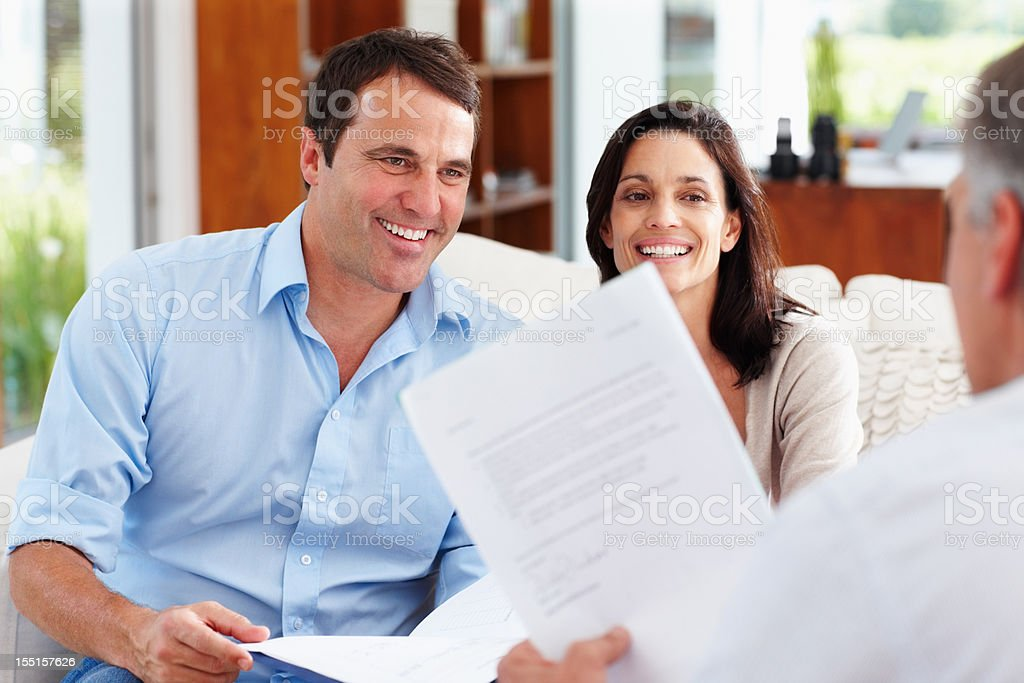 Happy couple planning future with paperwork royalty-free stock photo