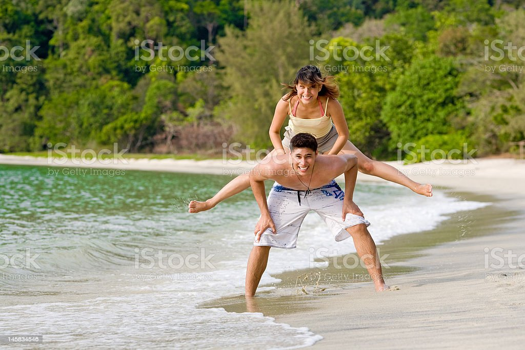happy couple playing leapfrog by the beach stock photo