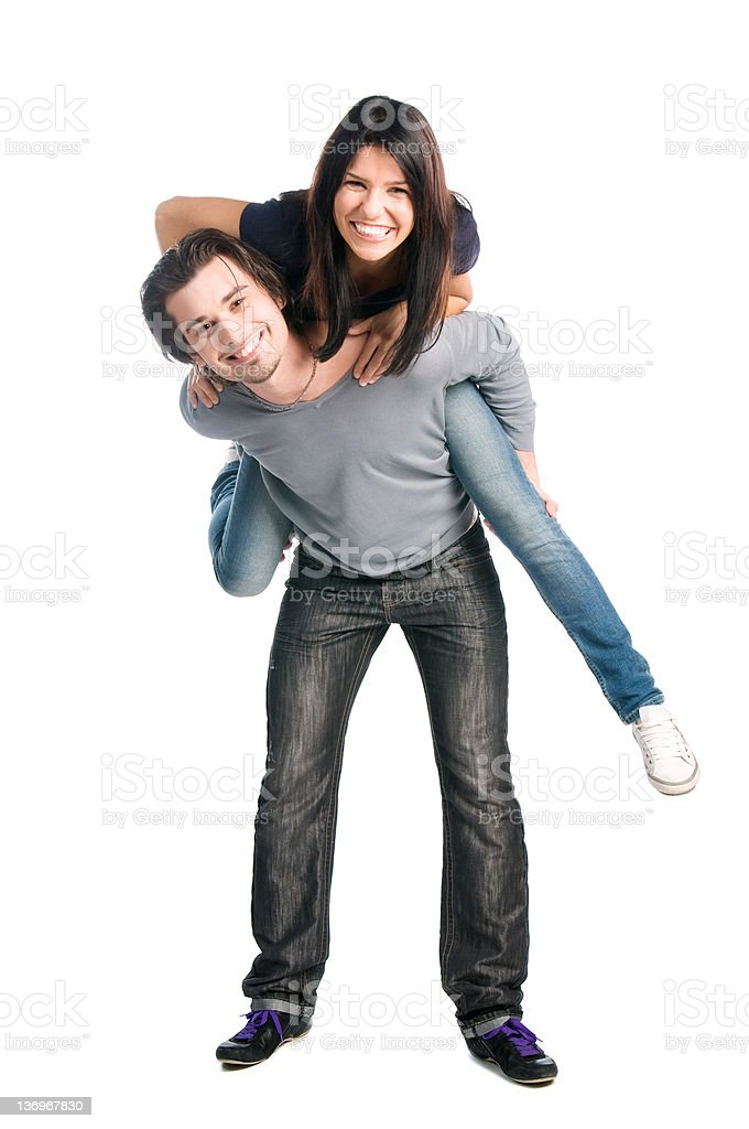 Happy couple playing piggyback together stock photo