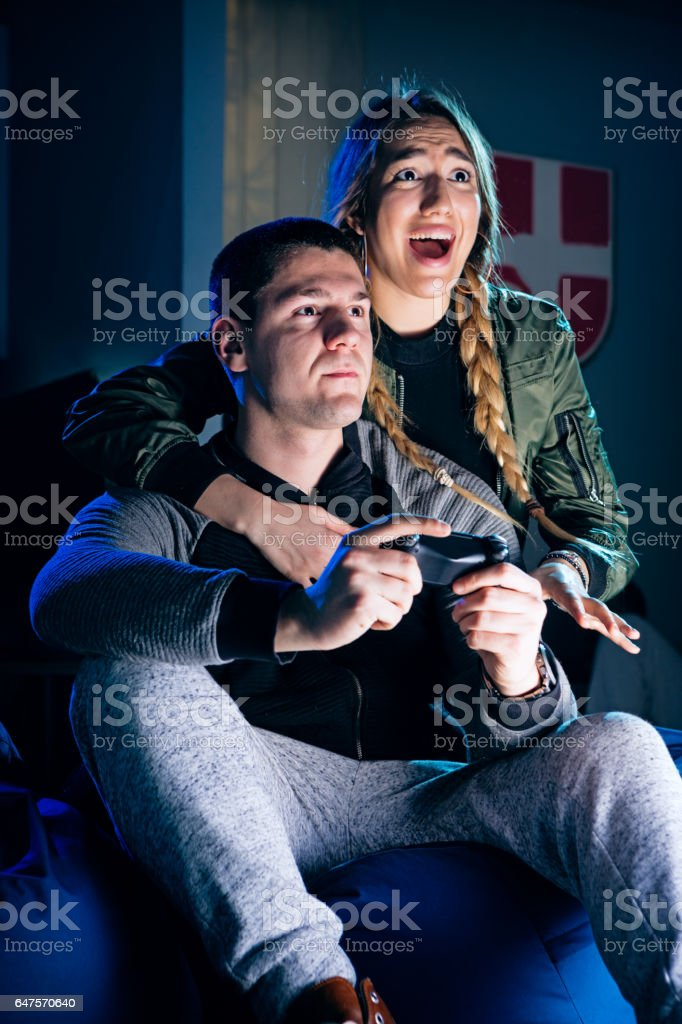 Happy couple playing video games and having fun together. stock photo